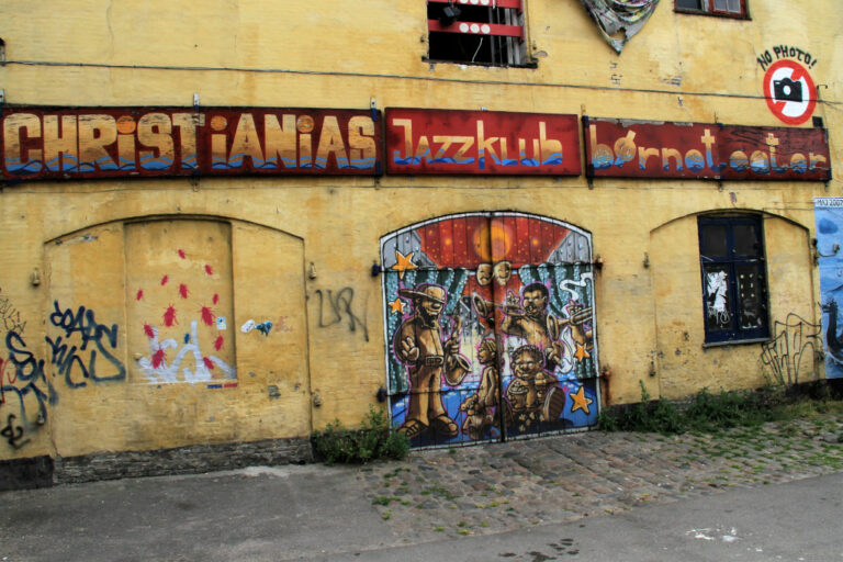 Graffiti spray painted on door and wall of building inside Christiania