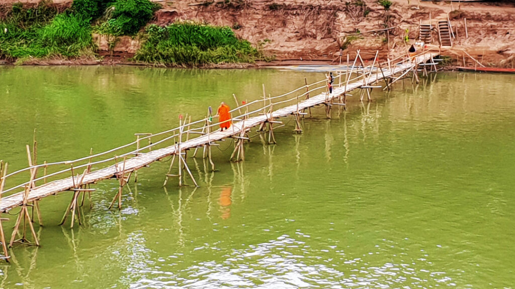 A monk walks on the bamboo bridge