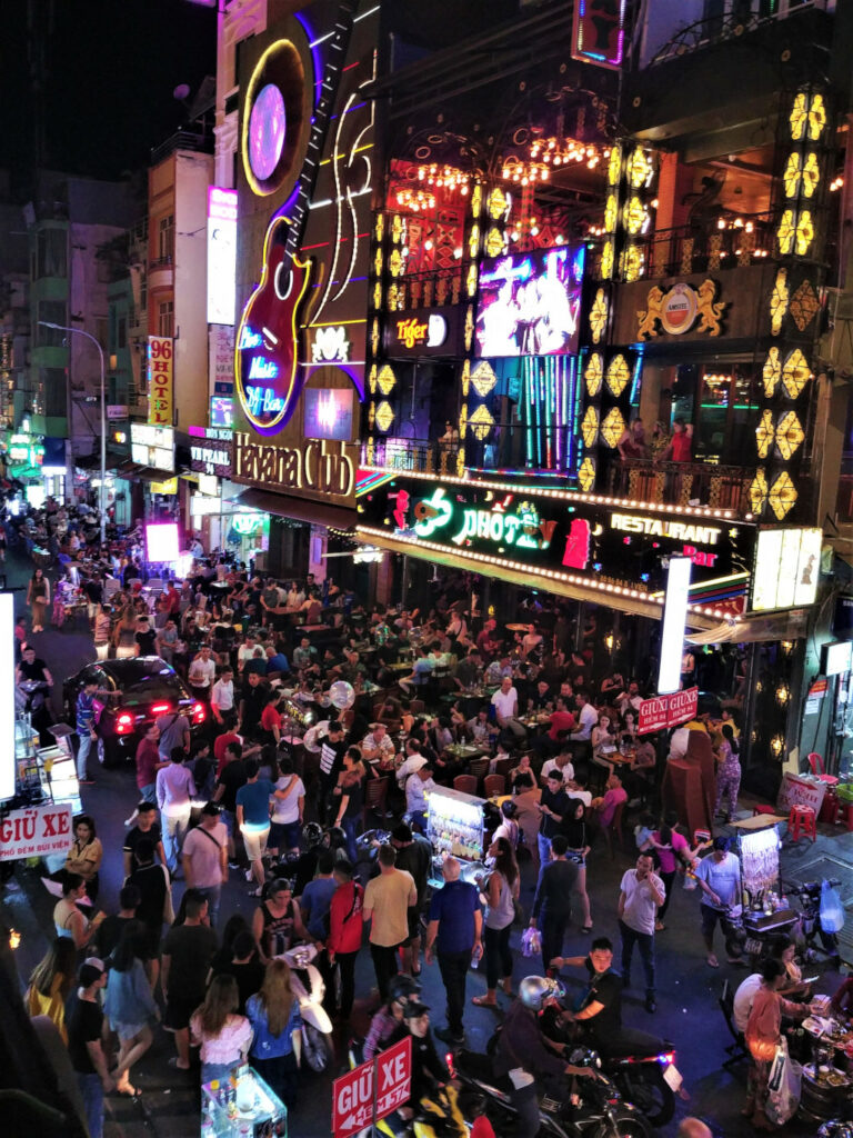 Crowded Bui Vien Street in Saigon Vietnam with brightly lit bars inviting tourists