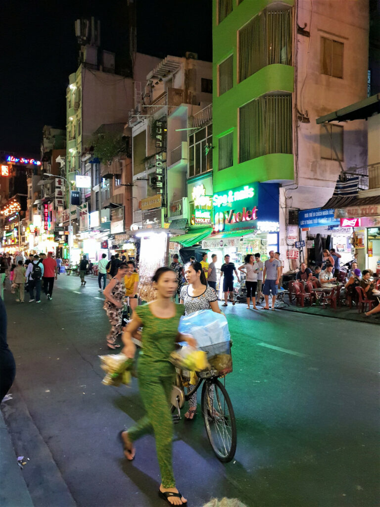 Busy night on Bui Vien Street in Saigon Vietnam with street vendors rushing to sell snacks