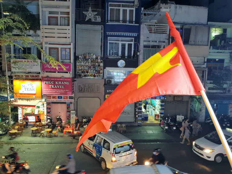 Street view from NAM Kitchen with Vietnam flag fluttering in Saigon Vietnam