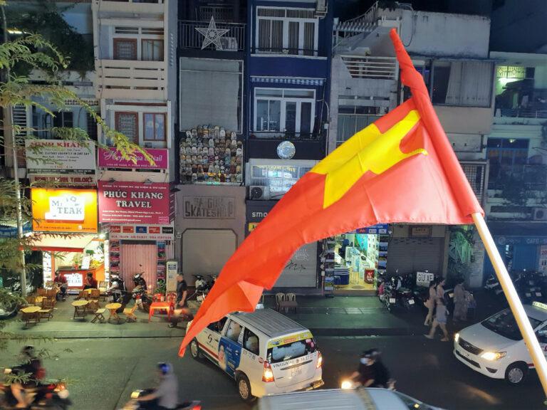 Street view from NAM Kitchen with Vietnam flag fluttering in Saigon Vietnam