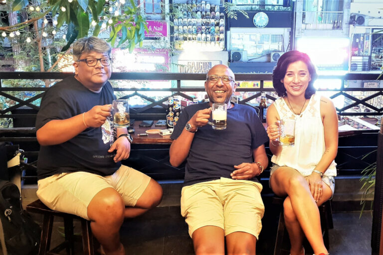 Three travellers catch up on beers and smiles at NAM Kitchen in Saigon Vietnam