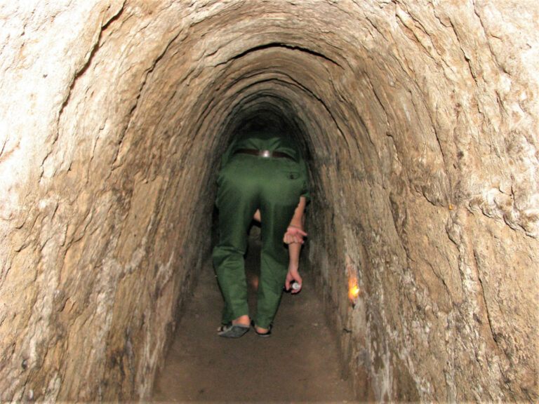 Guide crawling through Cu Chi tunnels as he leads the way
