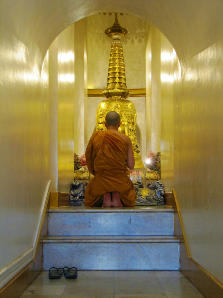 Buddhist monk praying inside Golden Mount