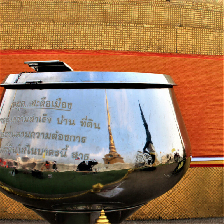 Stupa reflects on a donation collection box on the Golden Mount