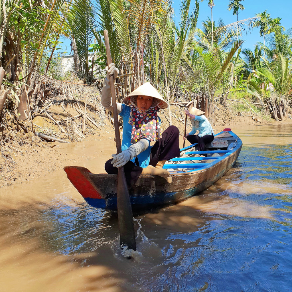Sailing on a sampan on a narrow canal in the Mekong Delta