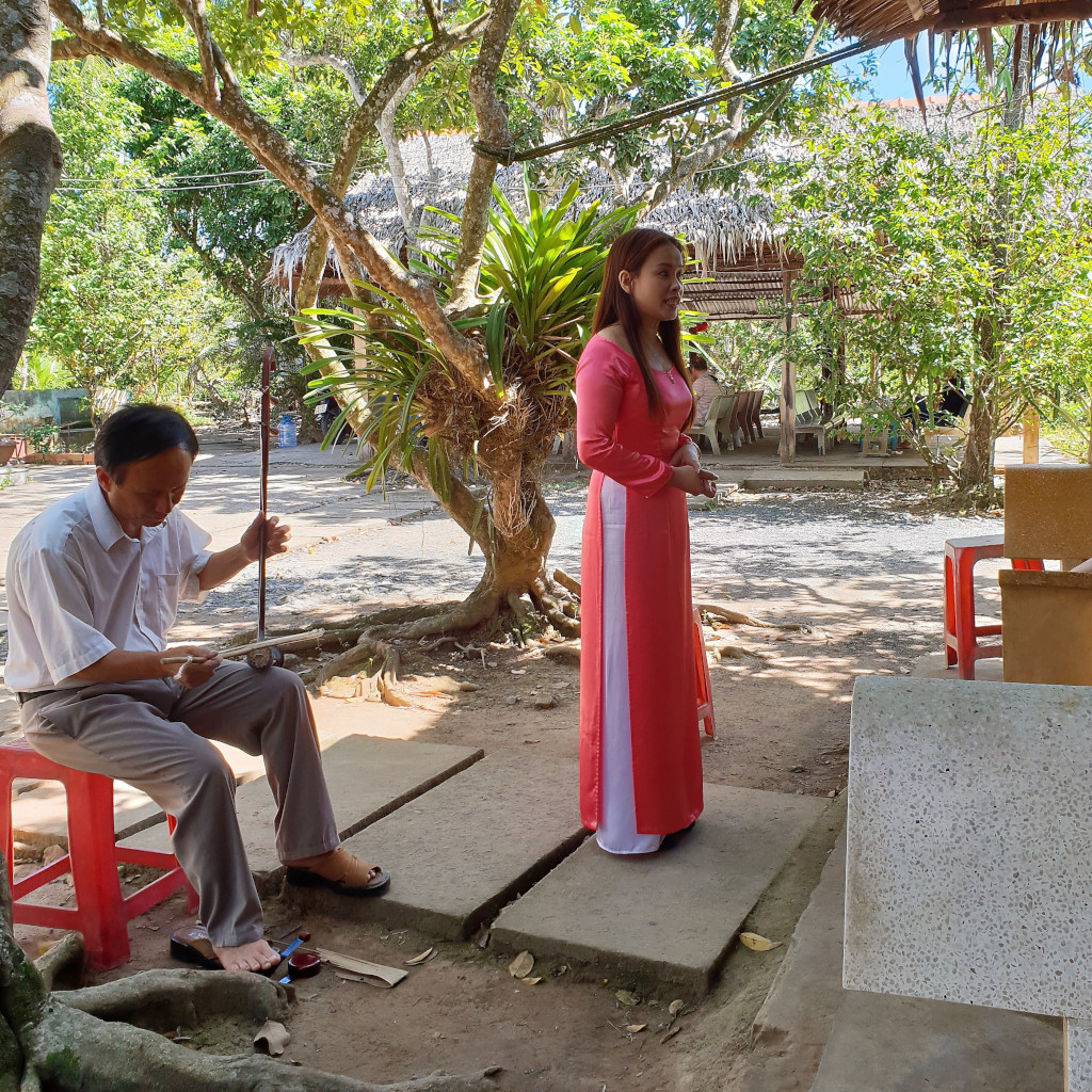 Singer entertaining tourists with folk songs in a Mekong Delta village