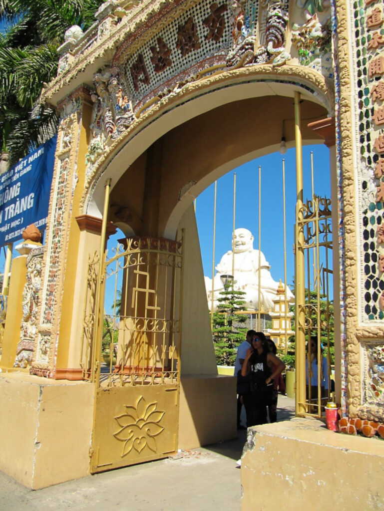 View of the smiling Buddha at Vinh Tranh pagoda from outside the gate