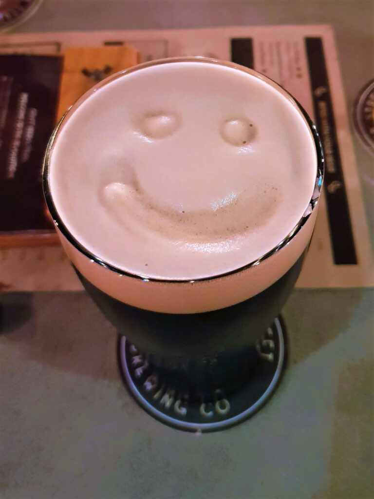 Side shot of a beer with a smiley drawn on the froth