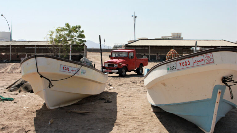 Functional Toyota Land Cruiser J series pickup with two fishing boats in the foreground.