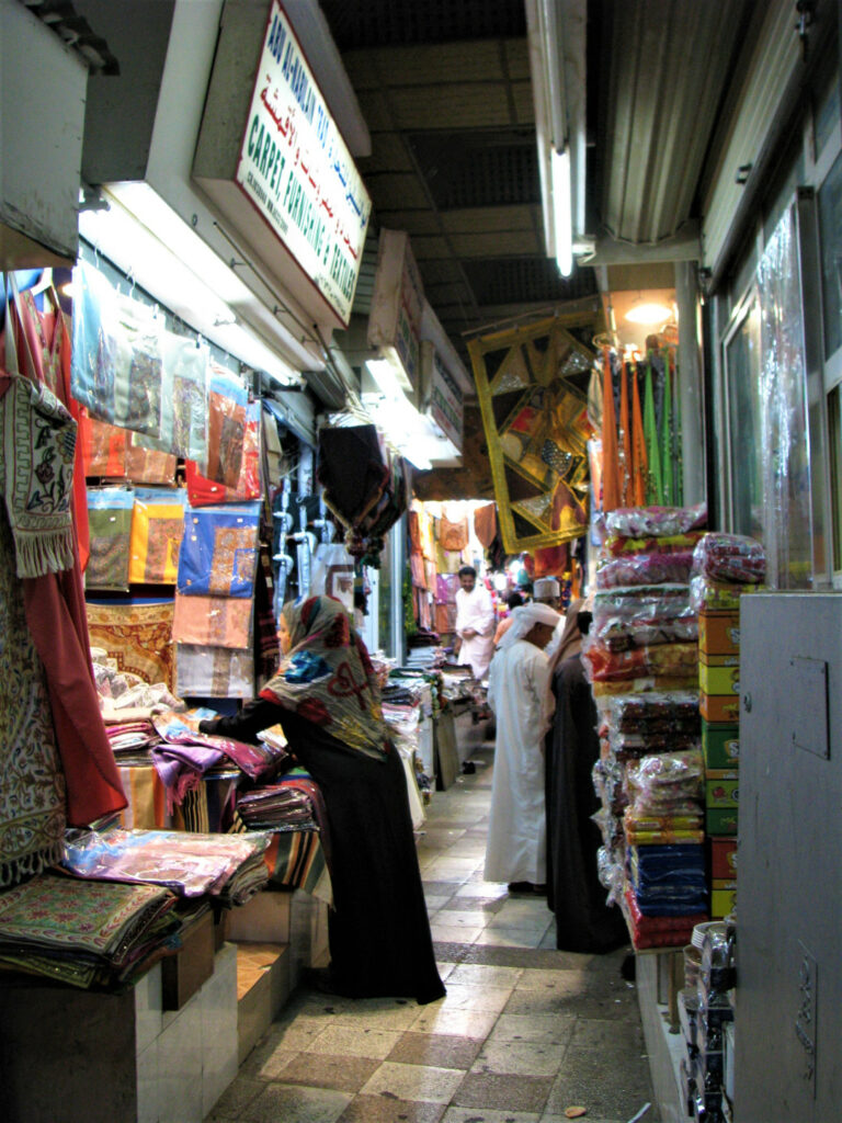 An Omani woman checking out fabrics at a store