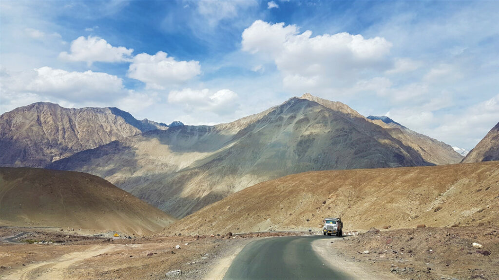 A solitary truck on the highway with the mountains acting as relief