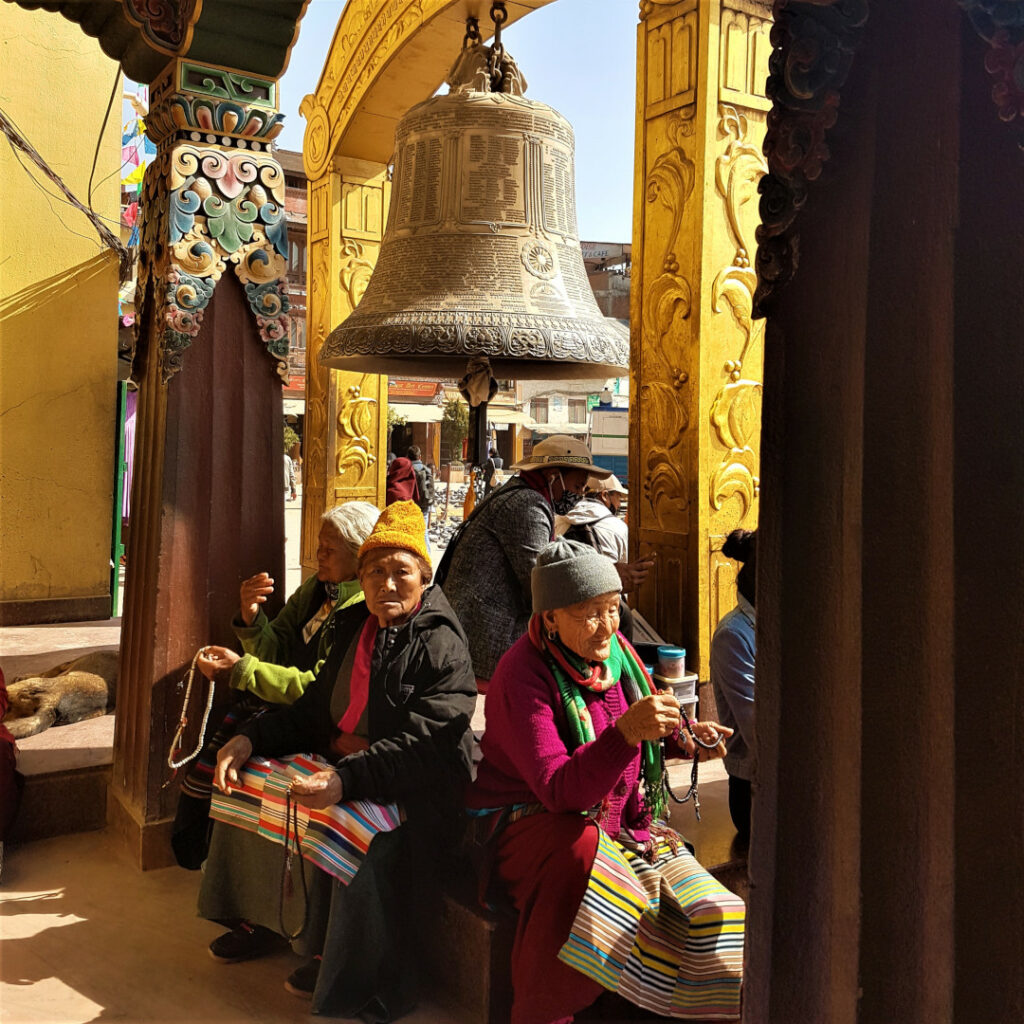 An old Tibetan looks on as she takes a break under the big bell at Boudhanath