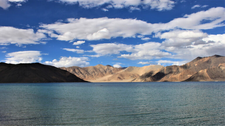 A panoramic view of Pangong Lake with the rugged mountains in the background