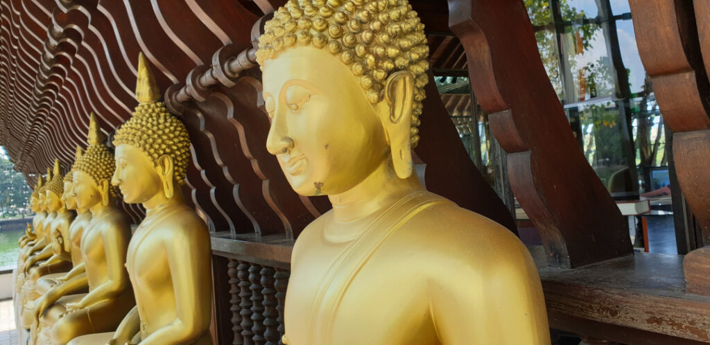 A row of Buddha statues outside the walls of the main temple