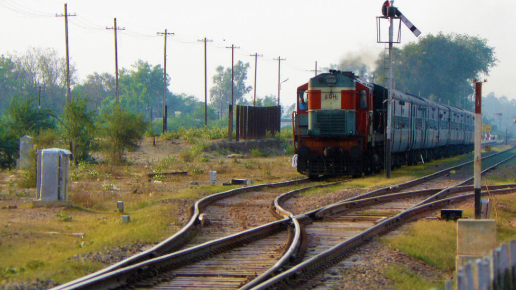 A diesel engine pulls along a passenger train in Punjab