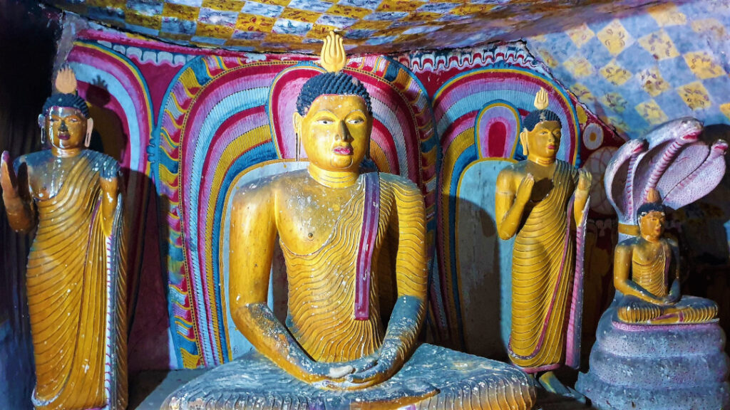 Statues of the Buddha with murals painted on the walls
