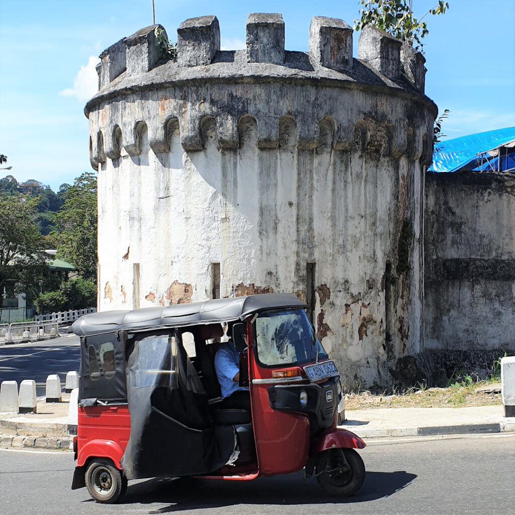 A tuk-tuk passes by the former prison