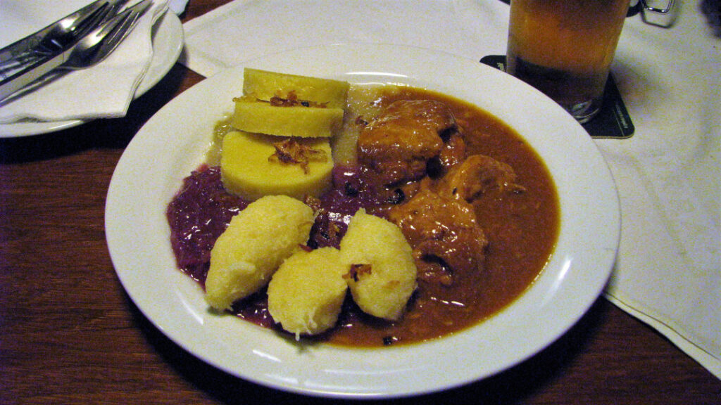A plate of goulash with dumplings